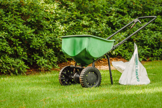 Manual walk behind grass seed spreader and bag of lawn fertilizer in a green residential backyard.