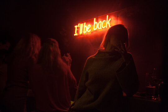 Silhouette of a smoking girl in a bar with a red neon light