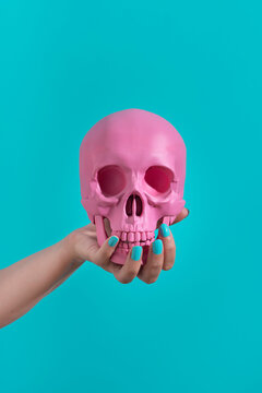 Female hand holding a pink skull