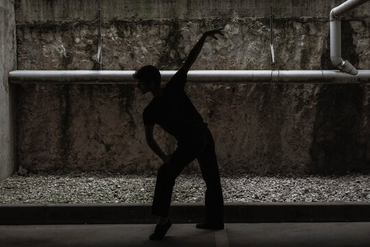 Young dancer performing on dark background