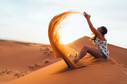 Young woman sitting on sand playing with sand ready for sandboarding
