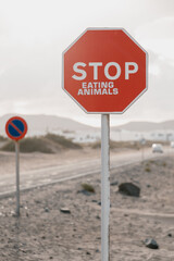 Road sign in mountains with rejection stop eating animals.