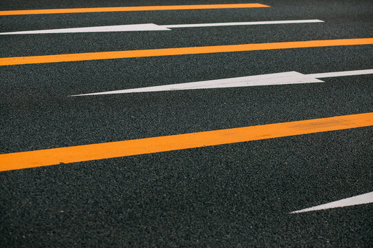 Directional arrows on an asphalted road.