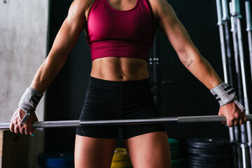Close up of muscular young fitness woman lifting a weight