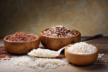 Four types of rice: basmati, mix long grain, arborio and red rice on wooden table.