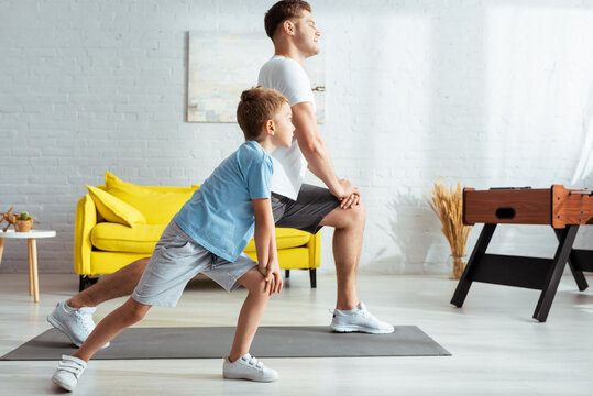 side view of young father and cute son doing lunges while exercising at home