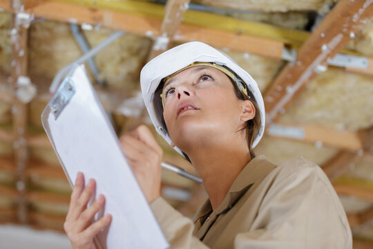 female inspector looking at ceiling in property to renovate