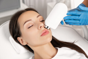 Elos epilation hair removal procedure on the face of a woman. Beautician doing laser rejuvenation in a beauty salon. Facial skin care. Hardware  ipl cosmetology