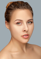 Portrait of a beautiful woman with  brown hair, beautiful fresh make-up and with healthy clean skin on a gray background. Make-up and cosmetology concept.