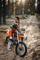 Beautiful female racer wearing motocross outfit with semi naked torso sitting on her bike in the forest