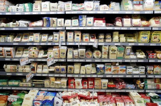 Various cheese products are displayed on a refrigerated shelf at a supermarket of Swiss retail group Migros in Zurich