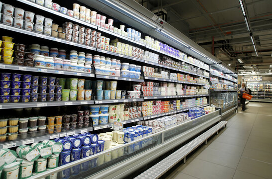Yogurts and other various milk products are displayed on a refrigerated shelf at a supermarket of Swiss retail group Migros in Zurich