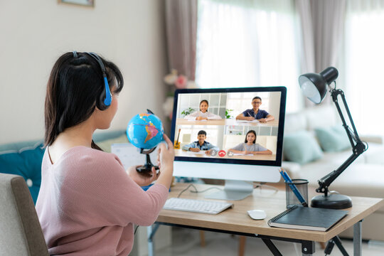 Asian woman teacher teaching geography via video conference e-learning and cheerful elementary school student looking at globe, Homeschooling and distance learning ,online ,education and internet..