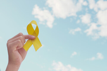Hands holding yellow gold ribbon over blue sky, Sarcoma Awareness, Bone cancer, childhood cancer...