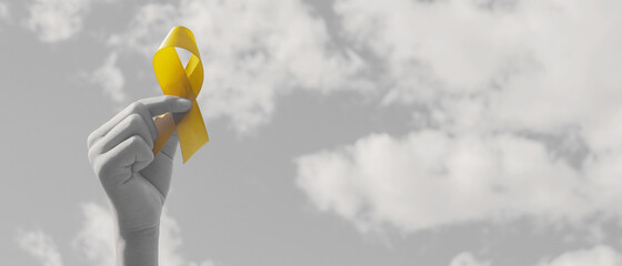 Hands holding yellow gold ribbon over  sky, Sarcoma Awareness, Bone cancer, childhood cancer awareness, September yellow, World Suicide Prevention Day concept