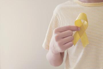 Hands holding yellow gold ribbon, Sarcoma Awareness, Bone cancer, childhood cancer awareness,...