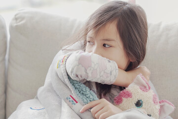 Mixed Asian sick girl coughing with her elbow at home, heath care concept