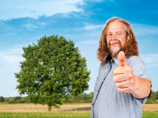 Older man shows thumbs up on field