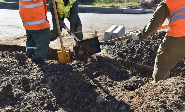 Workers throw earth with construction shovels, dig a hole for road curbs.