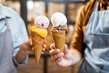 Two sellers cheering with yummy ice creams in waffle cone, having fun while selling ice cream at...
