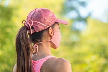 Corona virus face mask COVID-19 young healthy woman on outdoor walk wearing cloth string ties with...