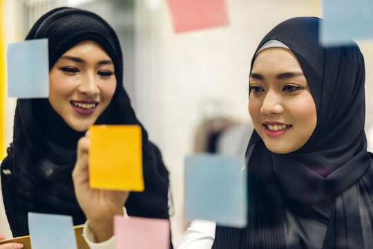 Casual creative happy two smile collegue two muslim business woman planning strategy analysis and brainstorm putting post it stickers note to share idea for startup project on glass window at office