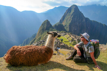 Tourist and llama sitting in front of Machu Picchu, Peru