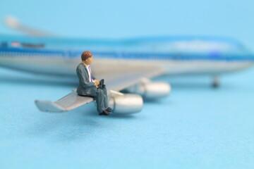kleines Flugzeugmodell mit eine Figur eines Geschäftsmannes