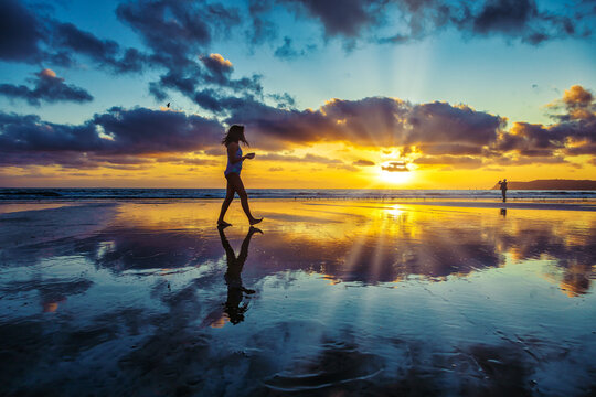 Low tide reflections at a beach with a cloudy sunset and silhouette of people
