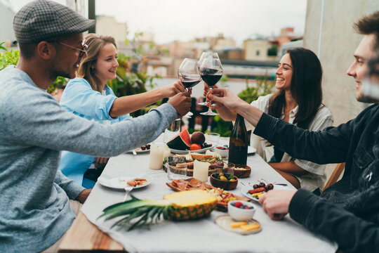 Group of happy people celebrating outdoors, Multiethnic group of young positive friends dining together on the rooftop or restaurant terrace celebrating, Summer Party Outdoors, Friendship Hanging Out