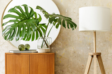 Beautiful composition at modern retro interior with design commode, tropical leaf in vase, round mirror, lamp, book, grunge wall and elegant accessories in stylish home decor.