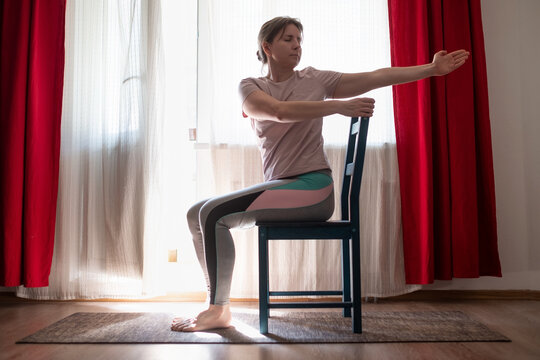 Woman working out doing yoga or pilates exercise using chair. Ardha Matsyendrasana pose variation.