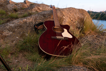 acoustic guitar on the rock. guitar at the sunset, music background concept