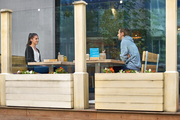 Young couple sit on the terrace according to the new rules of social distance. Conceptual new...