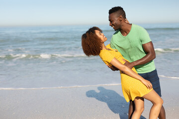 Mixed race couple dancing on the beach