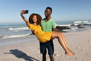 Mixed race couple taking selfies on the beach