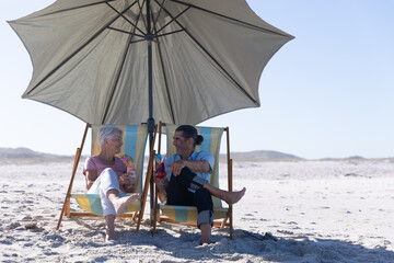 Senior Caucasian couple sitting on deck chairs at the beach.