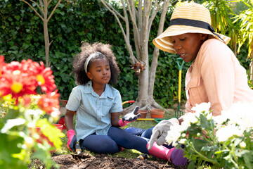 African American girl and her grandmother planting flowers at their garden