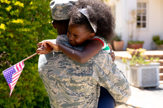 African American male soldier holding his daughter with a US flag in his arms