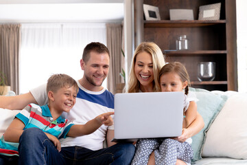 Caucasian family with two children using a laptop computer at home
