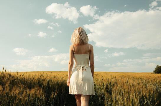 Beautiful blonde girl in wheat field in sunset time