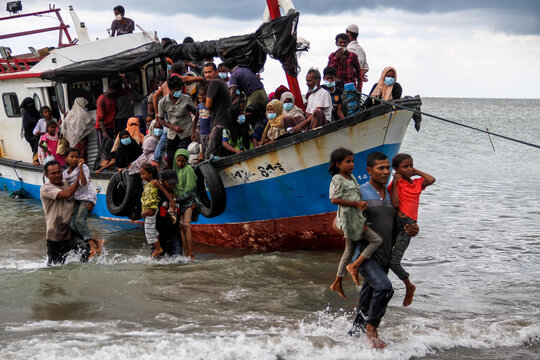 Locals evacuate Rohingya refugees from a boat at a coast of North Aceh
