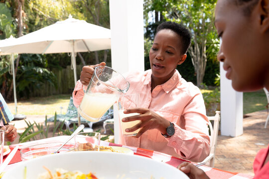 Senior African American woman pouring lemonade to a glass with his family in the garden