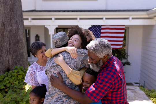 Multi-generation mixed race family welcoming an African American man wearing military uniform