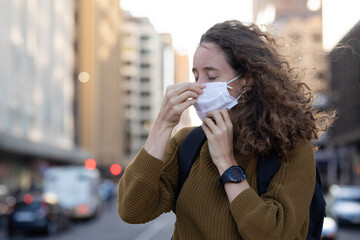 Caucasian woman putting on a protective mask in the streets