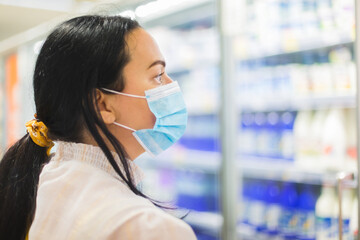 Woman buying food in supermarket. She is wearing protective mask and looking at the dairy section of a supermarket while shopping . Grocery shopping during COVID-19 concept. Selective focus