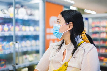 Grocery shopping during COVID-19. Woman wearing a protective face mask and looking at the dairy section of a supermarket while shopping. Selective focus, blank space