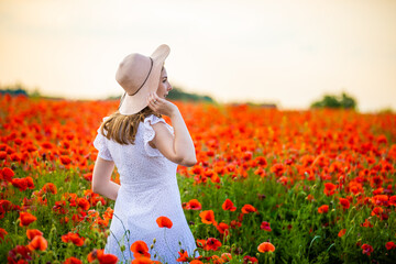 Woman with hat is standing in poppy field and enjoying a sunset, Czech republic