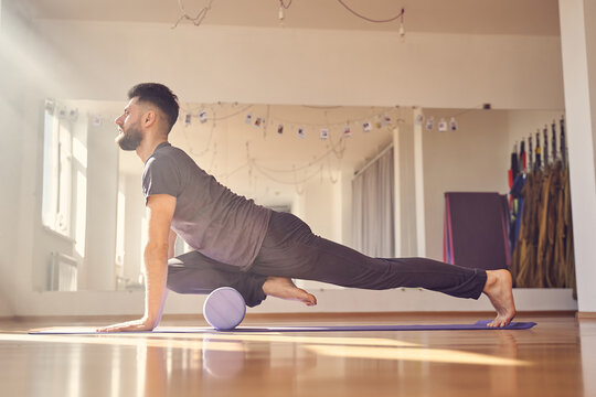 Handsome young man doing exercise with yoga foam roller