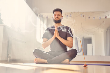 Serene young man meditating in yoga studio